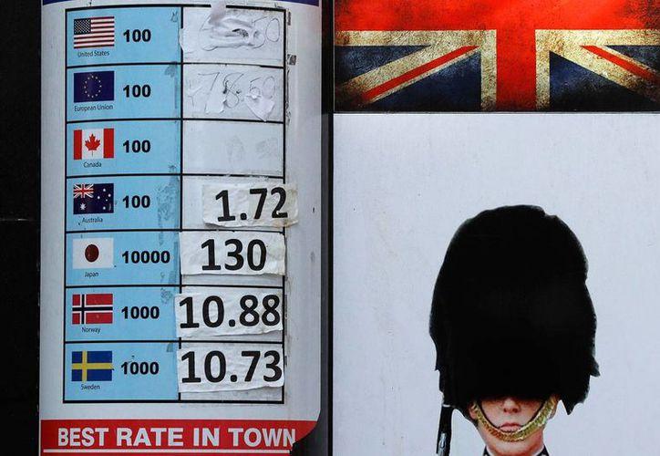 Foto del 12 de octubre del 2016, que muestra un anuncio de una casa de cambio en Londres. El valor de la libra esterlina ha estado cayendo en semanas recientes, pero británicos han encontrado que el nuevo billete plástico de cinco libras puede ser usado como aguja fonográfica. (AP Foto/Frank Augstein)
