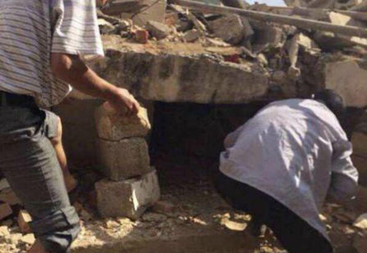 En la imagen, tomada por teléfono móvil de la Agencia de Noticias Xinhua de China, hombres buscan entre los escombros de edificios sobrevivientes después de un terremoto en el condado de Ludian de Zhaotong ciudad de la provincia suroccidental china de Yunnan. (Agencias)