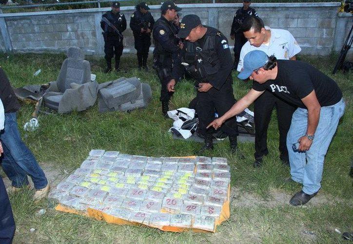 Agentes antinarcóticos muestran el dinero decomisado. (EFE)
