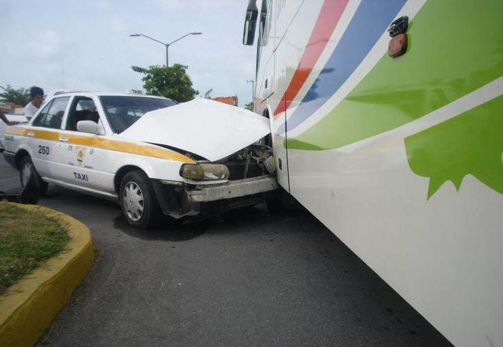La unidad de taxi fue proyectada contra el autobús en el que viajaban los niños. (Redacción/SIPSE)