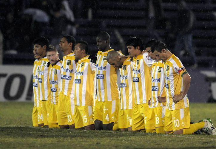 Los jugadores de The Strongest de Bolivia se arrodillan en la cancha durante la tanda de penales que el equipo perdió el martes 29 de abril de 2014 ante Defensor Sporting de Uruguay en la Copa Libertadores. (AP)
