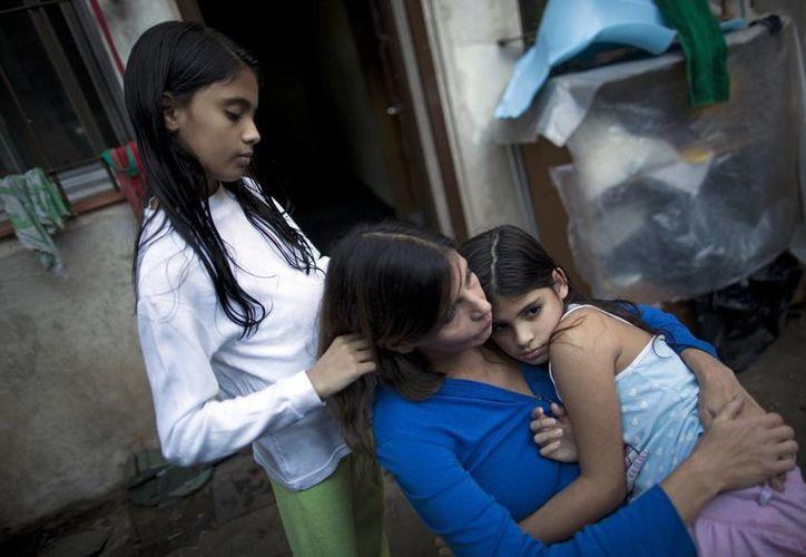 Andrea Nerone (c), descansa con sus hijas Malena, derecha, y Candela en su hogar durante una entrevista en Buenos Aires, Argentina. (Agencias)