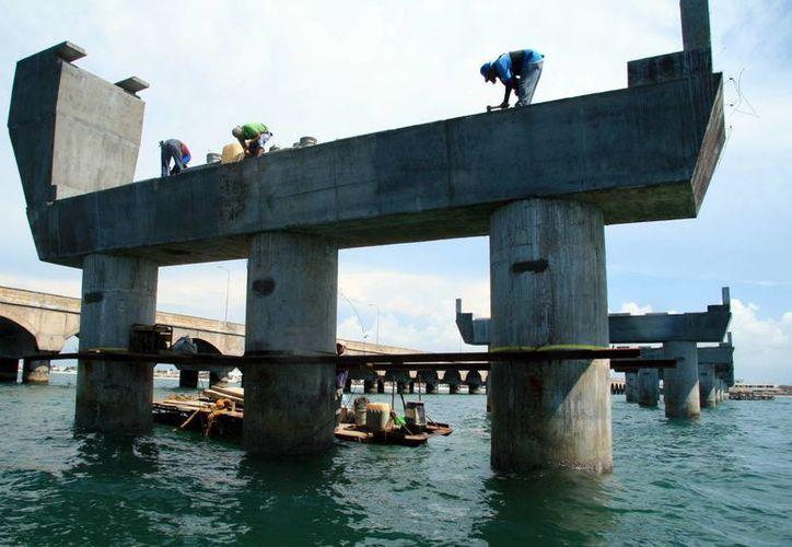 Los trabajadores asignados para parchar las columnas lo hacen sin las medidas mínimas de seguridad. (Fotos: SIPSE)