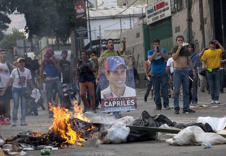 Los manifestantes, uno sosteniendo un cartel del candidato presidencial opositor Henrique Capriles, frente a la policía antimotines en el barrio Altamira en Caracas. (Agencias)