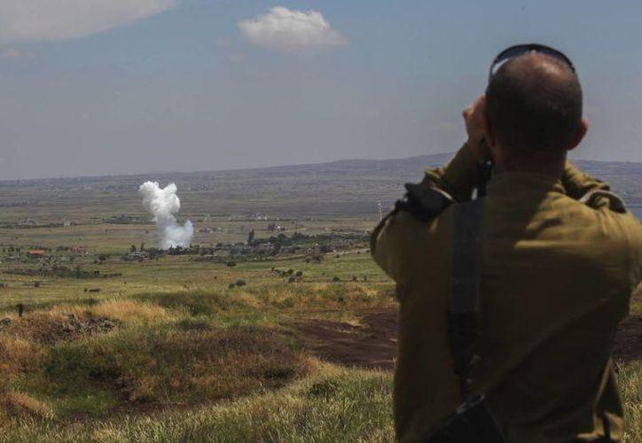 Un soldado israelí observa el humo ocasionado por el bombardeo de la armada siria, fiel al presidente Bashar Assad, en el pueblo sirio de Qahtaniya, capturado por los rebeldes. (EFE/Archivo)