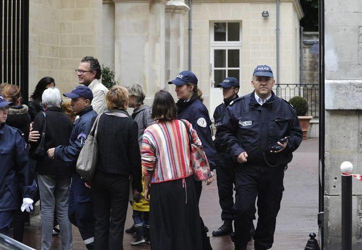 Padres se llevan a sus hijos de la escuela infantil de La Rochefoucauld, en Paris, después de la tragedia. (EFE)
