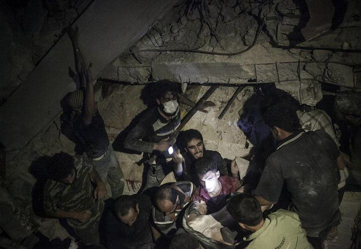 Aldeanos sirios tratab de rescatar a las víctimas de un edificio destruido debido a un ataque aéreo. (Agencias)