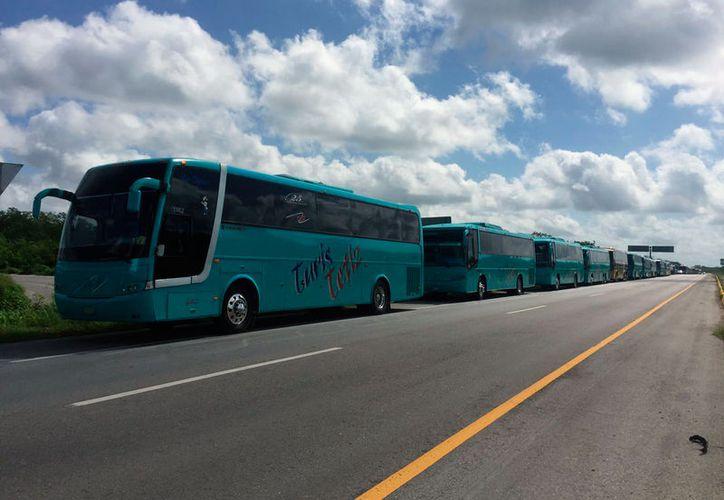 En la carretera Mérida-Campeche, varios autobuses se estacionaron en al carril de acotamiento, a manera de protesta por iniciativas que pretenden sacar de circulación camiones de más de 20 años de antigüedad. (Gretel Mac/SIPSE)
