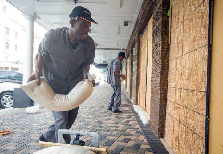 Perry Williams y Alaric Nixon colocan sacos de arena ante el escaparate de la tienda Diamond's International al prepararse para el Huracán Joaquín en Nassau, Bahamas. El fenómeno metereológico provocó grandes inundaciones en su paso por las islas del este de Bahamas como una tormenta de categoría 4. (AP Foto/Tim Aylen)