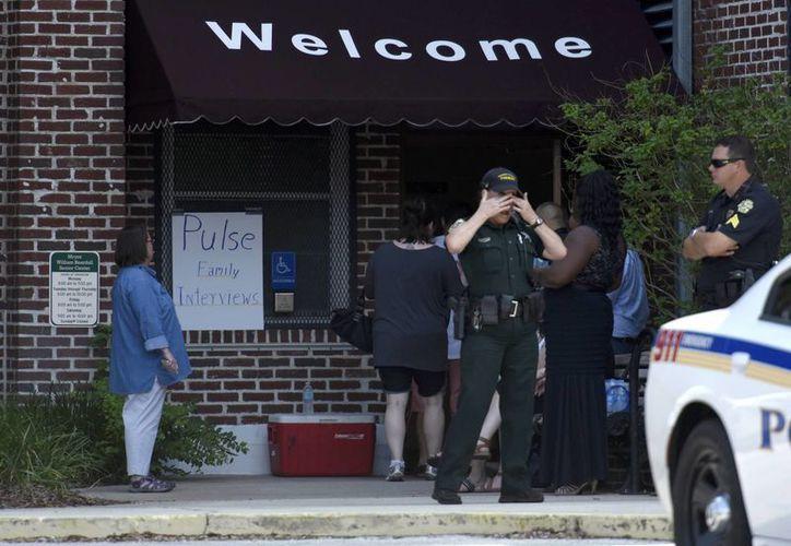 Un sheriff se limpia el rostro mientras familiares de víctimas del tiroteo en el club nocturno Pulse arriban a un centro de reunificación instalado en el Geriátrico Beardall, el lunes 13 de junio de 2016, en el Orlando, Fla. (Foto: Chris Urso/The Tampa vía AP)