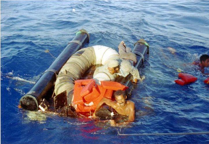 Foto del 11 de septiembre de 1994 en el que se ve a tres cubanos remolcados de una balsa 'hehiza' hacia una embarcación de la Guardia Costera de los Estados Unidose, a unos 15 millas al norte de Cuba. (Foto de archivo: AP/Alon Reininger)