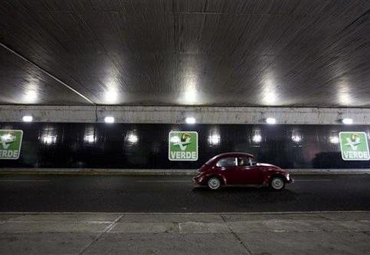 Un auto transita junto a carteles del Partido Verde Ecologista de México en un paso subterráneo en la Ciudad de México. (Agencias)