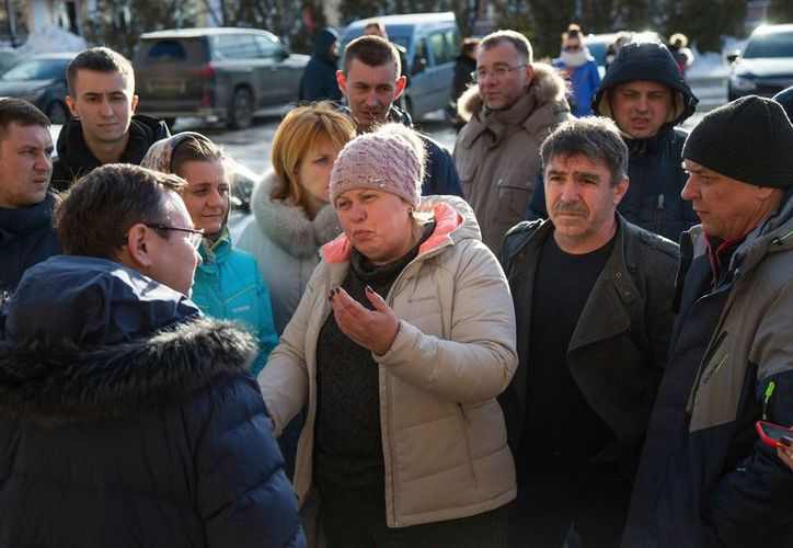 People argue with a local administrator, left, about the reported air poisoning in Volokolamsk, 100 kilometers (62 miles) west of Moscow, Russia.