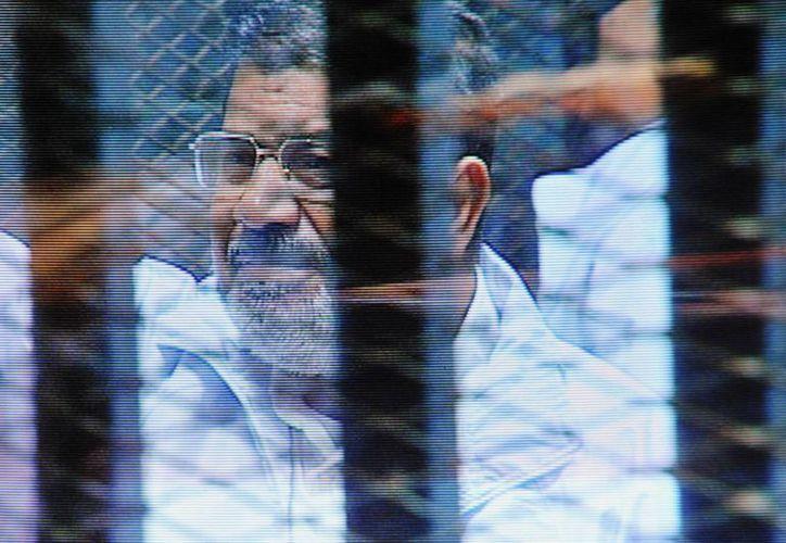 En esta foto del domingo 16 de febrero del 2014 se ve al derrocado presidente egipcio Mohamed Morsi en una jaula frente a un tribunal. (Agencias)