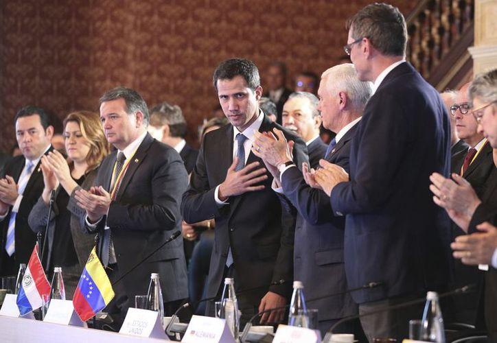 Flanqueado por el vicepresidente Mike Pence, centro derecha, el autoproclamado presidente interino de Venezuela, Juan Guaidó, saluda al Grupo de Lima, en Bogotá, Colombia. (AP)