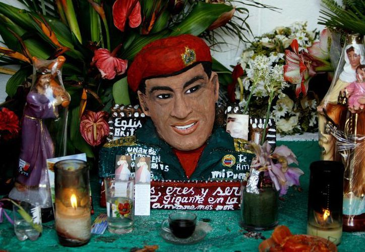 Un busto del fallecido presidente venezolano Hugo Chávez está adornado con flores, velas e imágenes religiosas en una capilla levantada en su honor. (Agencias)