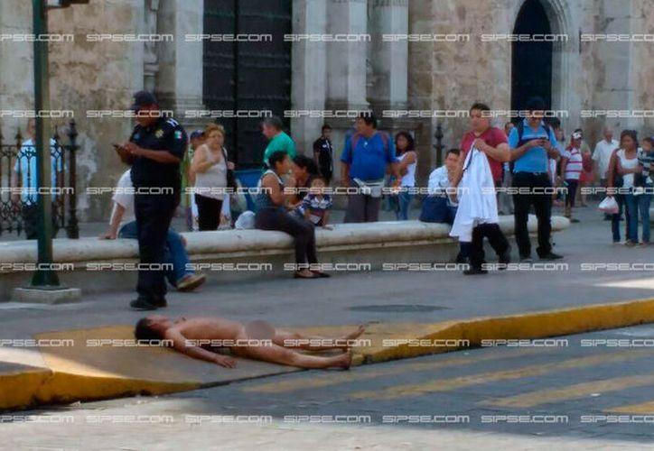 Un hombre se desnudó y se acostó frente a la Catedral de Mérida, en protesta por supuestos maltratos de los policías. (Paty Iztá/SIPSE)