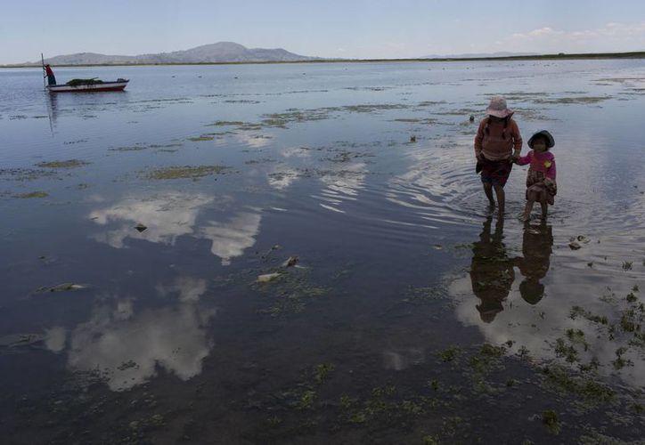Dos primos de la familia Ávila buscan juguetes abandonados en la orilla del lago Titicaca, en Coata, en la región de Puno, Perú. (AP/Rodrigo Abd)
