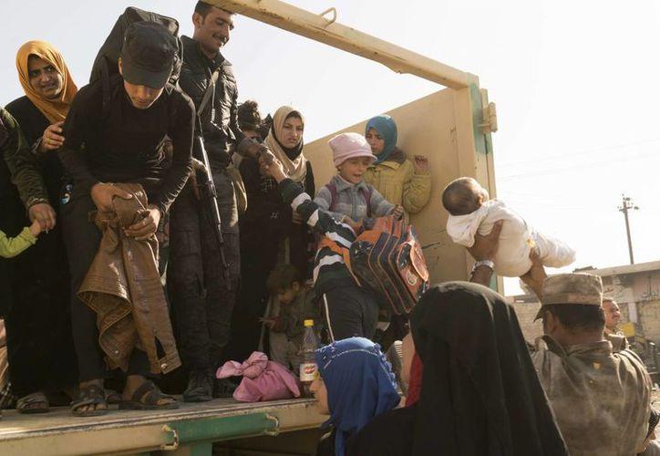 Soldados iraquíes ayudan a mujeres y niños que huyeron de Mosul a subir a camiones para viajar hasta campos de refugiados. (AP/Nish Nalbandian)