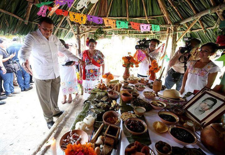 En la imagen, el gobernador de Yucatán, Rolando Zapata Bello admirando uno de los altares de la Gran Muestra Estatal de Altares Hanal Pixán en la Plaza Grande. (José Acosta/SIPSE)