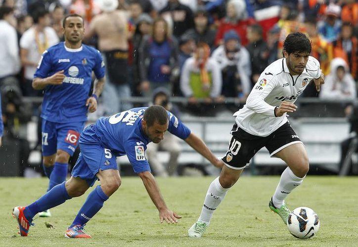 El centrocampista del Valencia, Éver Banega (d), avanza con el balón mientras es perseguido por el argelino del Getafe Mehdi Lacen. (EFE)