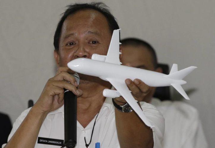 El investigador del gobierno indonesio Ertata Lananggalih usa un modelo de avión para mostrar la inclinación que tomó el avión de AirAsia que cumplía el vuelo 8501 antes de estrellarse en el Mar de Java en diciembre del año pasado, durante una conferencia de prensa en Yakarta, Indonesia. (Agencias)