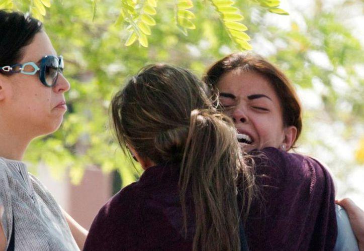 Familiares de los pasajeros de un avión de EgyptAir que se estrelló se abrazan a las afueras del aeropuerto de El Cairo, tras conocerse la noticia de la catástrofe aérea. (AP)