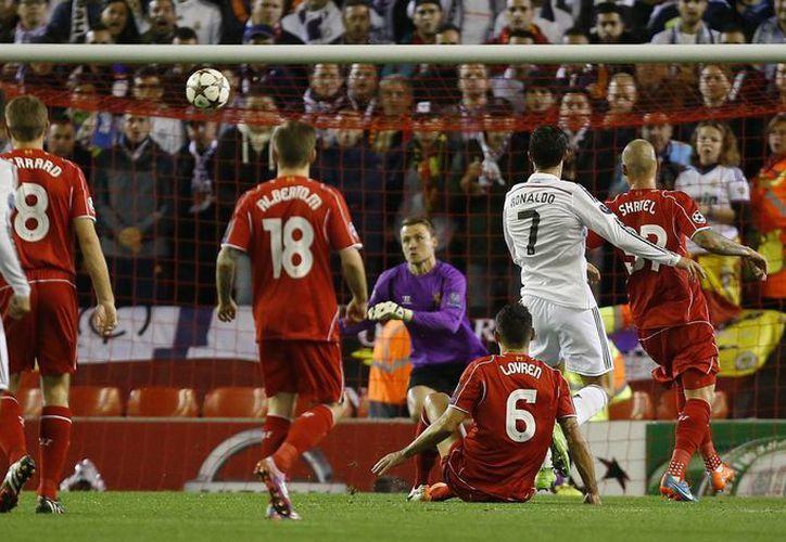 Cristiano Ronaldo (d) recibió un extraordinario pase globeado de James Rodríguez por la derecha del área grande y de bote pronto cuchareó la pelota hacia el angulo derecho del arquero rival, que no pudo evitar el gol 70 del portugués en la UEFA Champions League.(Foto: AP)