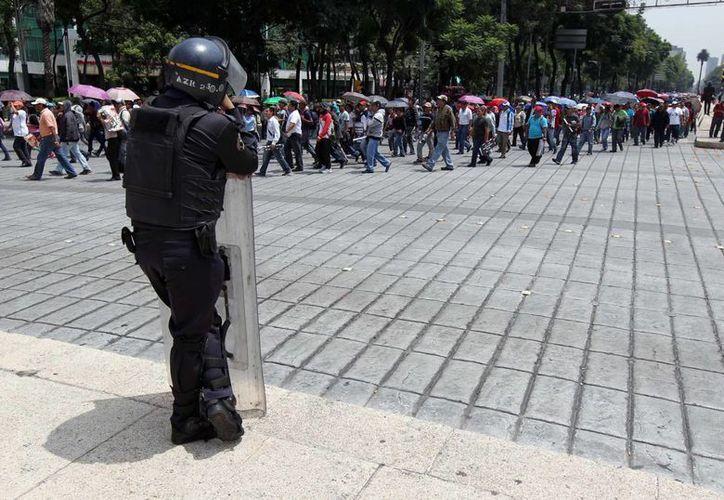 Elementos de la Secretaría de Seguridad Pública del Distrito Federal resguardaron edificios públicos y privados durante el paso de la marcha de los maestros de la CNTE por Paseo de la Reforma. (Notimex)