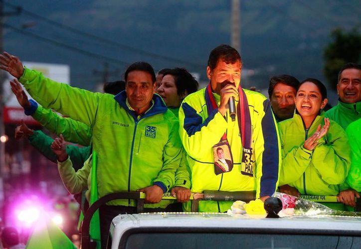 Rafael Correa (c), quien fue registrado este lunes, saluda a sus simpatizantes en un recorrido por las calles de Quito. (EFE)
