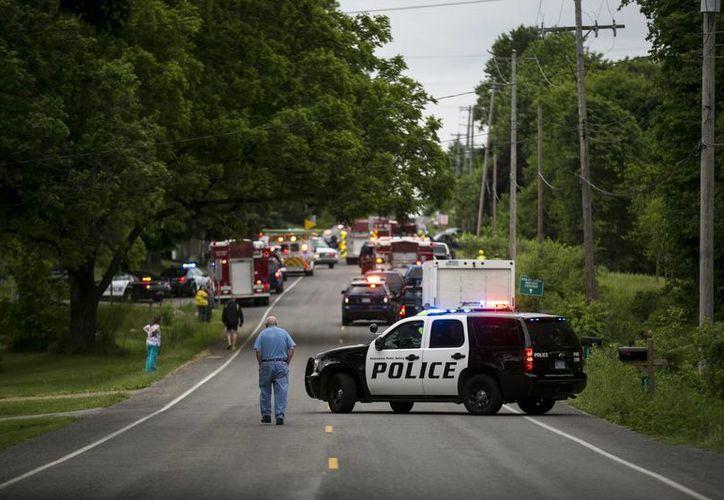 Policías y rescatistas acuden al sitio donde fueron atropellados fatalmente varios ciclistas, el martes 7 de junio de 2016, en Copper Township, Michigan. (Chelsea Purgahn/Kalamazoo Gazette-MLive Media Group vía AP)