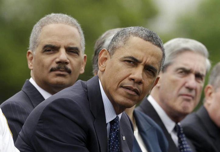 Obama (centro) ayer en Washington con el procurador Eric Holder (izq.) y el jefe del FBI, Robert Mueller. (Agencias)