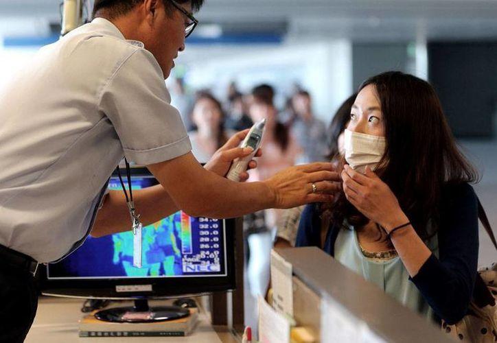 Personal de salubridad de un aeropuerto de Corea del Sur monitorea la temperatura de una pasajera que retornó de África, como un medida preventiva para evitar la llegada del ébola. La OMS declaró ya emergencia internacional por la epidemia. (AP)