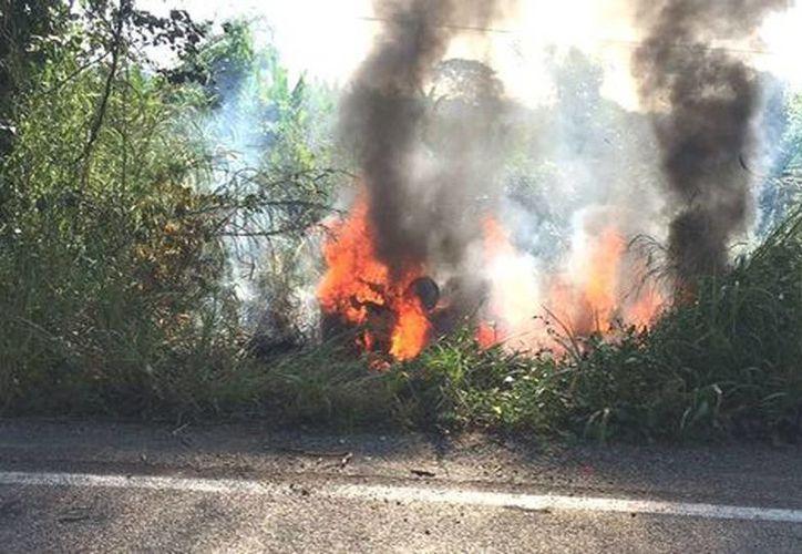 Cerca del mediodía, el automóvil marca Topaz en que circulaban tres personas fue baleado y quemado a un costado de la carretera, en Tabasco. (Mariel Arroyo/Milenio)