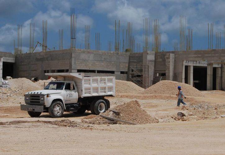 Alrededor de 100 trabajadores apuran sus tiempos para alcanzar la meta de edificación. (Tomás Álvarez/SIPSE)