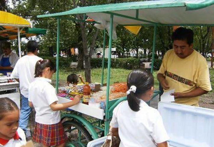 Comer en lugares higiénicos evita problemas de salud. Imagen de un grupo de escolares que compran alimentos de dudosa procedencia. (Milenio Novedades)