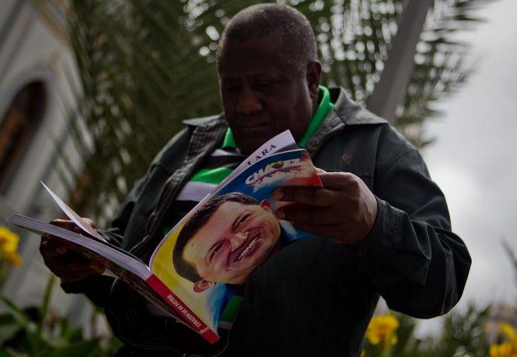 Un hombre sostiene un libro con la imagen del presidente Hugo Chávez este 24 de diciembre, en el centro de Caracas (Venezuela). EFE