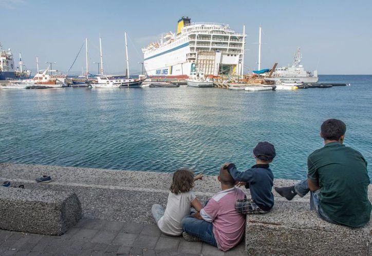 Refugiados sirios esperan para embarcar en la nave de procesamiento de refugiados en el puerto de Kos, en la isla griega de Kos, Grecia. (EFE)