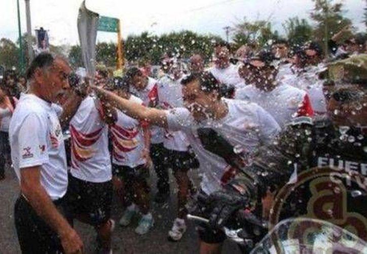 Momento en que estudiantes protestan y apagan la antorcha de los Juegos Centroamericanos y del Caribe en Veracruz. (Foto de Milenio tomada de Al Calor político)