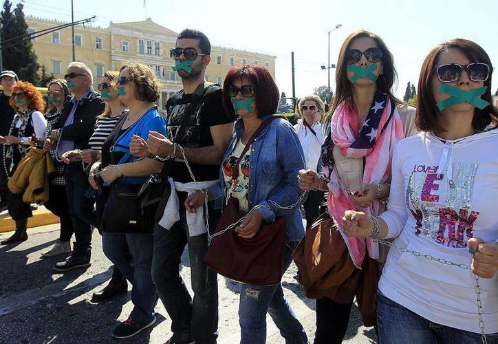 Trabajadores de organizaciones sociales se manifiestan encadenados y con mordazas en el centro de Atenas, durante una protesta el pasado 3 de abril. (Archivo/EFE)
