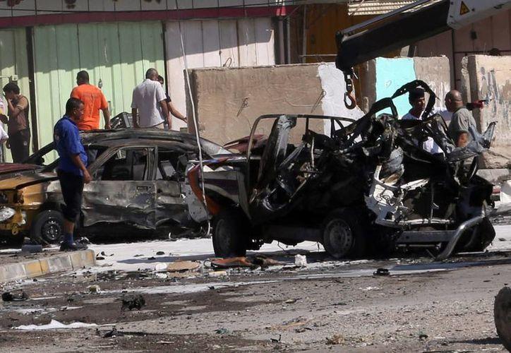 inspección ciudadana en la zona de un atentado con coche bomba en Bagdad. (Agencias)