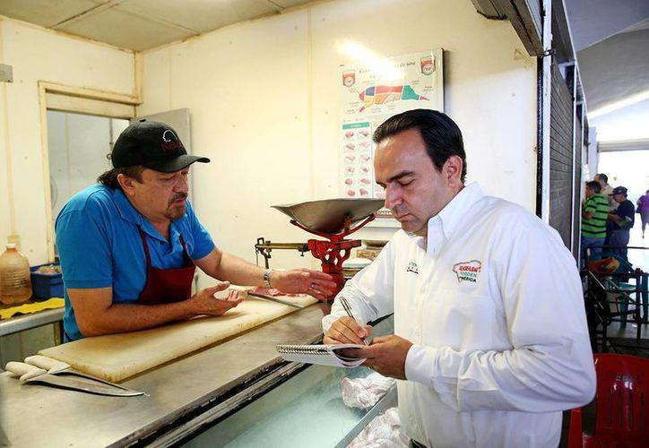 Nerio Torres Arcila toma nota de las peticiones de un locatario del mercado de Santa Ana. (SIPSE)