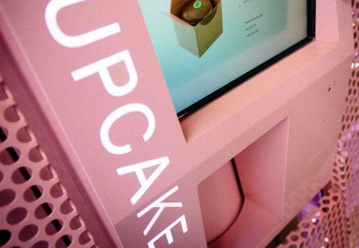 """Imagen de la campaña publictaria de la empresa pastelera """"Sprinkles Cupcakes"""" con un niño observando un ATM de """"cupcakes"""", en Nueva yORK. (EFE)"""