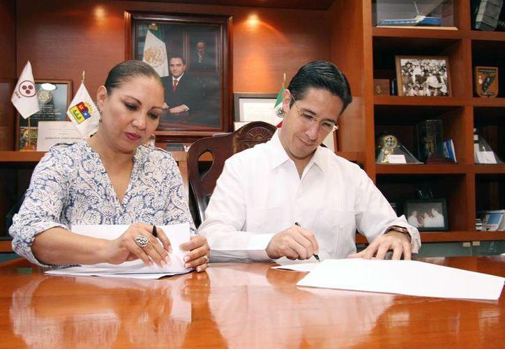 La delegada de la Profepa y el alcalde de la isla firmando el convenio. (Cortesía/SIPSE)