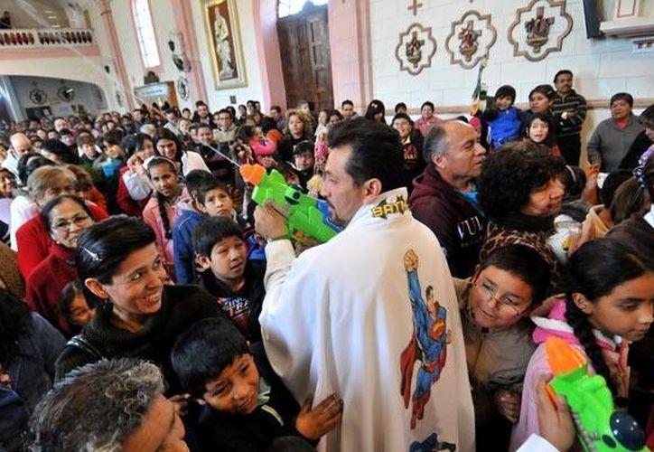 """El padre Humberto """"disparando agua bendita"""" durante la misa en su parroquia. Nótese a Superman en su sotana. (www.Vanguardia.com.mx)"""