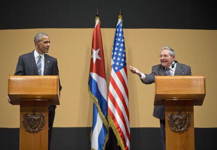 El presidente Barack Obama escucha como el mandatario de Cuba, Raúl Castro le responde al periodista que lo cuestiono sobre los presos políticos. (Agencias)