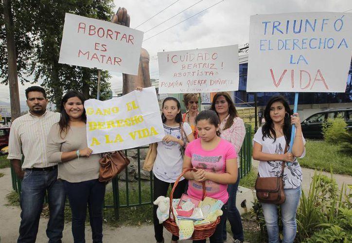 """Miembros de la fundación Sí a la Vida sostienen carteles frente al monumento """"Sí a la Vida"""" en San Salvador. (Archivo/EFE)"""