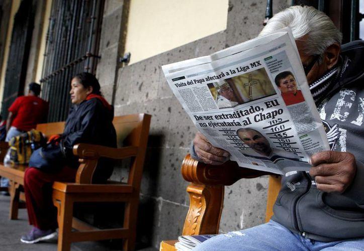 Un hombre lee un periódico donde se da la noticia una noticia sobre 'El Chapo', quien logró notoriedad internacional con una primera fuga de prisión en 2001, cuando huyó de la cárcel de Puerto Grande, en Guadalajara, oculto en un carro de la lavandería. (Archivo/EFE)