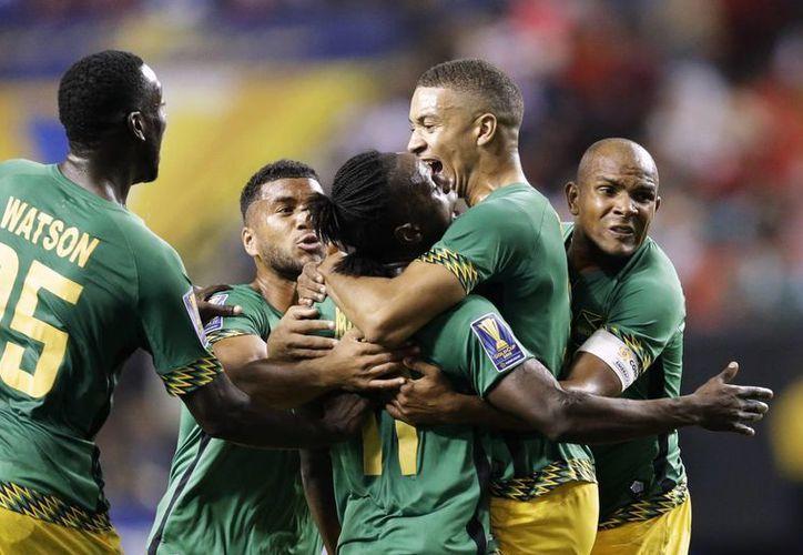 Darren Mattocks (c), de Jamaica, recibe un abrazo de sus compañeros, entre ellos Michael Hector (d), después de anotar uno de los goles con su selección ganó a EU 2-1 para eliminarlo en la semifinal de la Copa Oro. (Foto: AP)