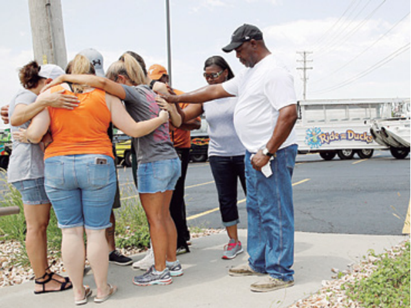 People pray outside Ride the Ducks, an amphibious tour operator involved in a boating accident on Table Rock Lake, in Branson, Mo. (AP)